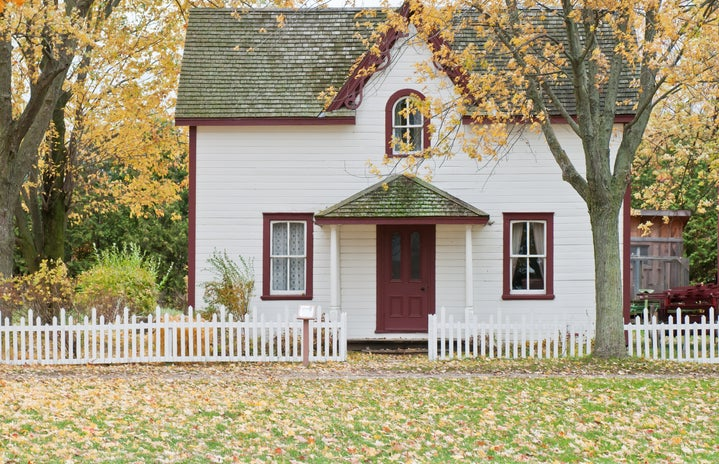 Small house on an autumn's day. The house is white and there are bare trees in front of it.