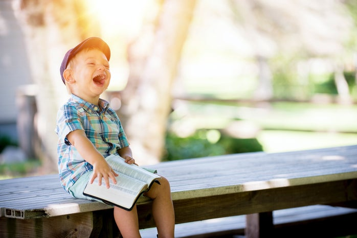 young boy sitting on bench while smiling