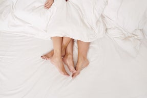 couple's feet sticking out the sheets