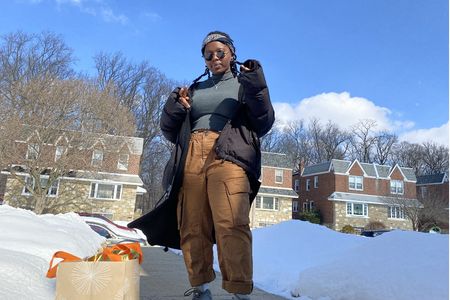 woman standing in front of houses with snow on the ground
