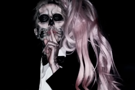 Lady Gaga in a skull makeup, pink hair and indicator finger on her mouth