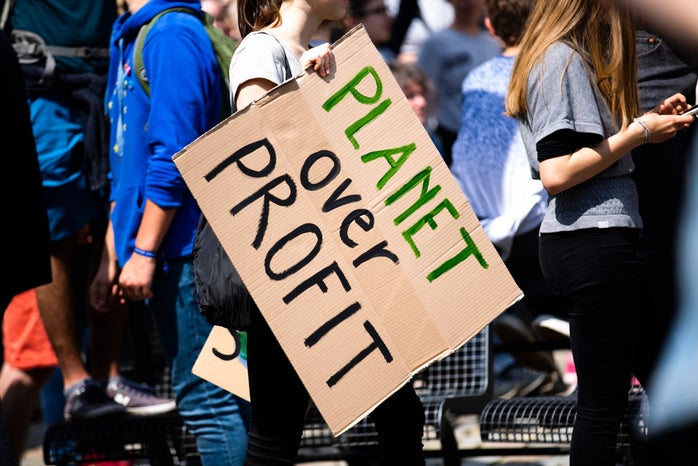 """person holding a sign that says """"planet over profit"""""""
