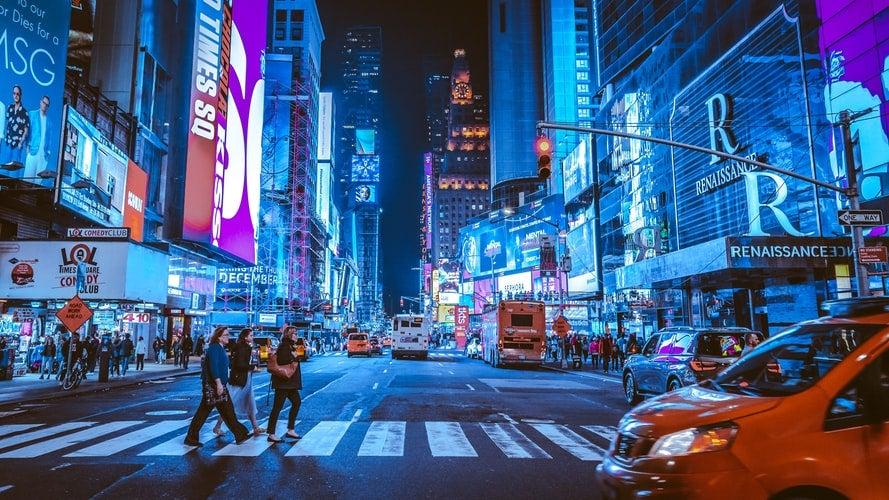 people walking on crosswalk in NYC at nighttime