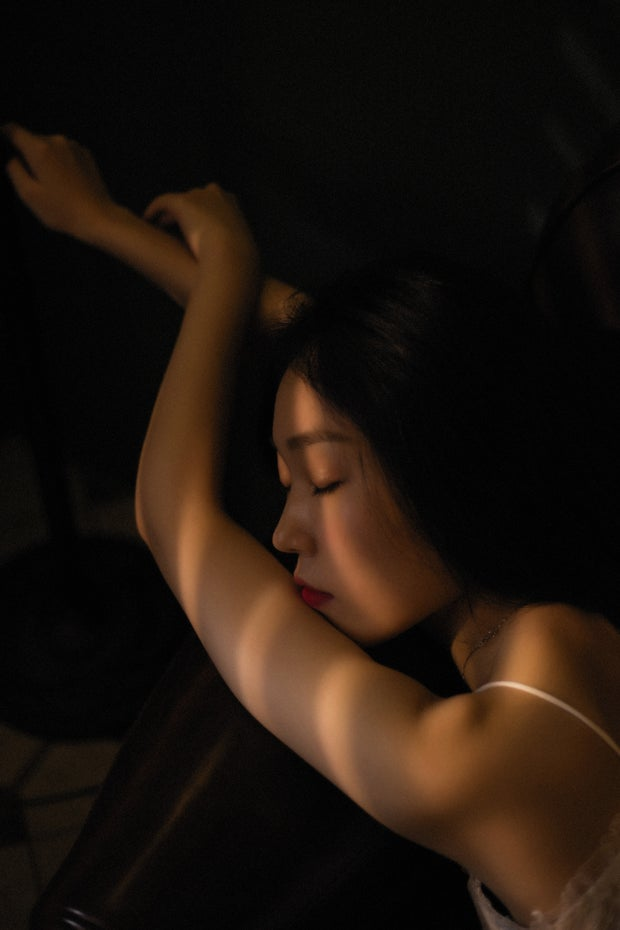 Woman poses in shadowy lighting.