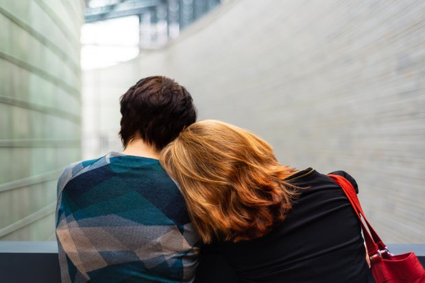 two people resting their heads on each other's shoulders, backs facing the camera