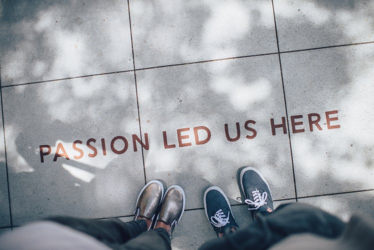 """Two people standing on paved gray tiles that read, \""""Passion led us here.\"""""""