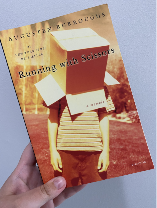 my hand holding the book Running with Scissors by Augusten Burroughs