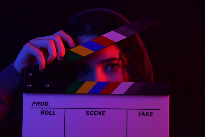 Woman holding a colorful clapperboard in a dark background