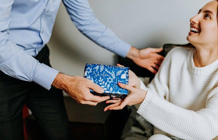 woman receiving wrapped hanukkah present