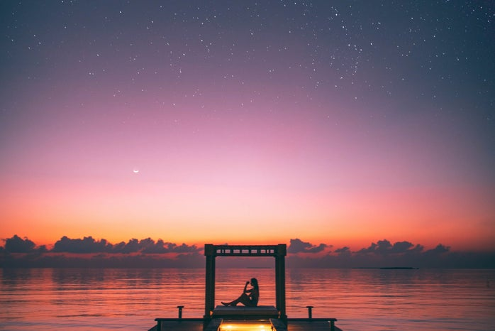 Person Sitting on Boardwalk at sunset