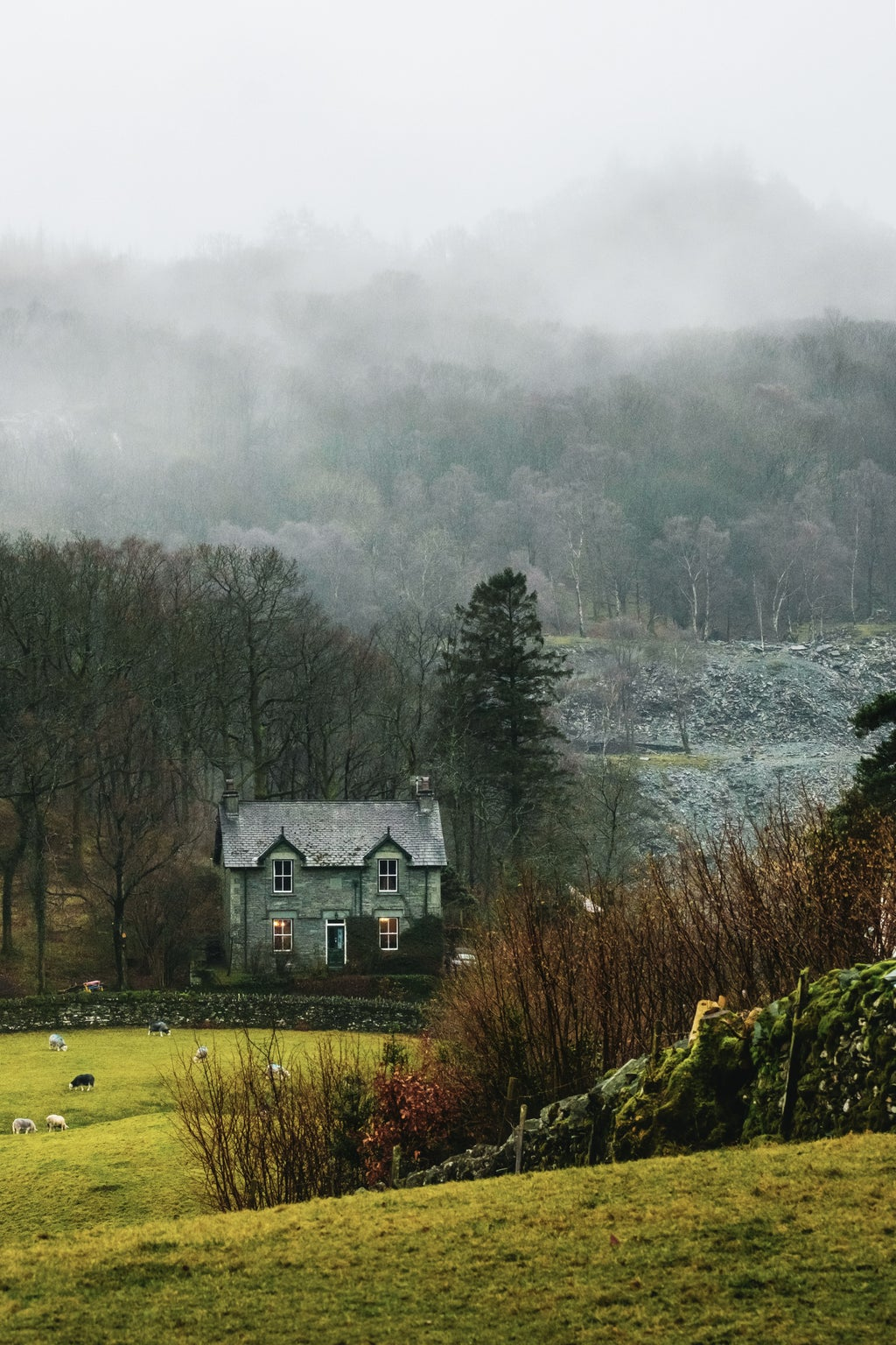 Old cottage surrounded by farm fields and forests in the Lake District