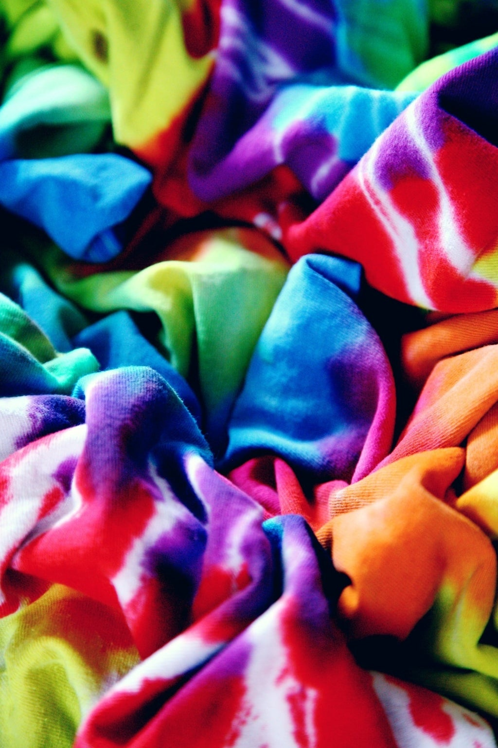closeup of scrunched tie dye shirts in rainbow colors