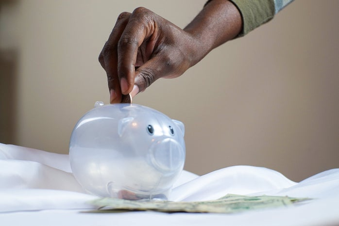 Hand inserting coin into plastic piggy bank
