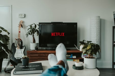 Anonymous individual holds onto a remote, which is directed towards the TV screen (displaying the typical Netflix slogan), on what seems to be his/her living-room/bedroom.