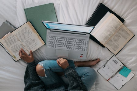 Woman sitting on bed with laptop and books