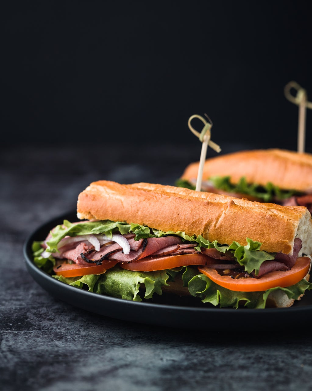 vegetabes and sliced deli meat on roll