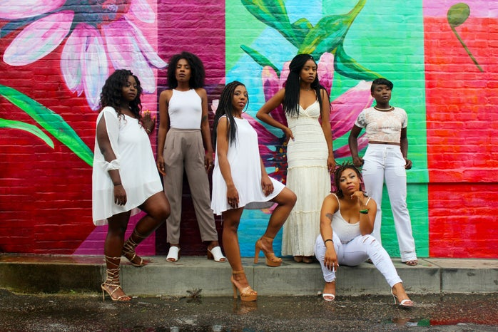 six Black women in white standing against a floral wall