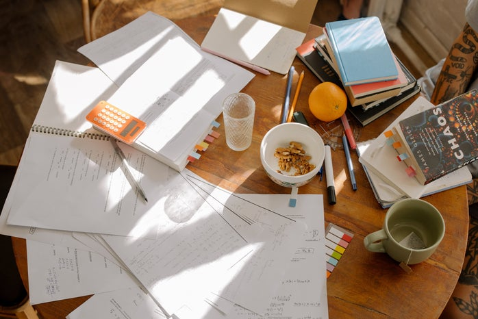 study notes and books on a brown wooden table