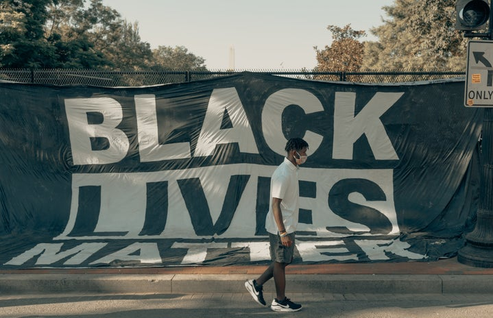 Black Lives Matter sign with man walking in front of it