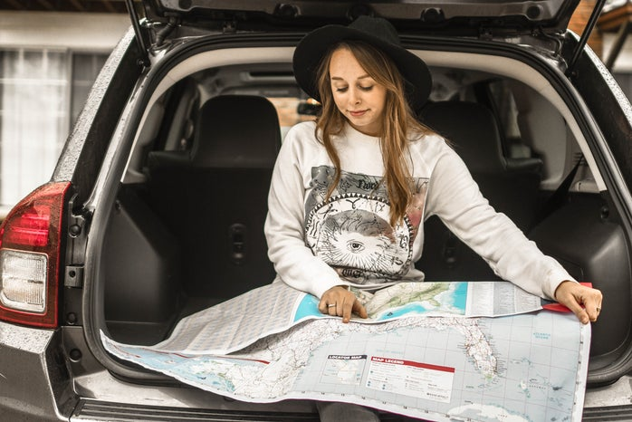 A woman looking at a map in the back of her car.