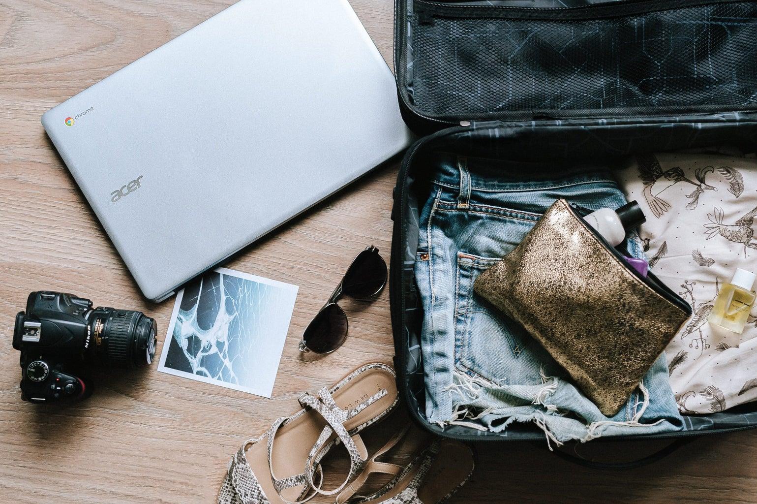 black DSLR camera near sunglasses and travel bag