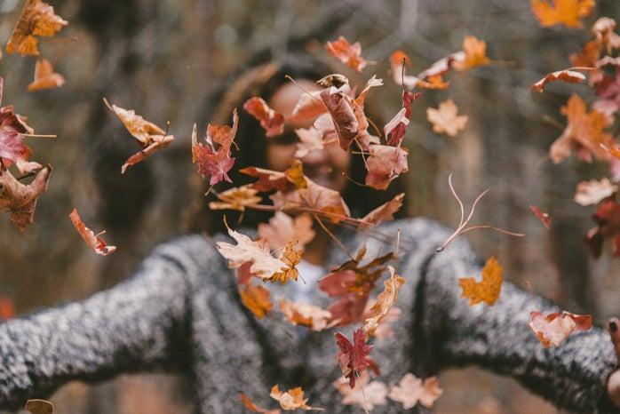 Women throwing fall leaves
