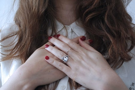 brunette girl with red nail polish and wedding ring