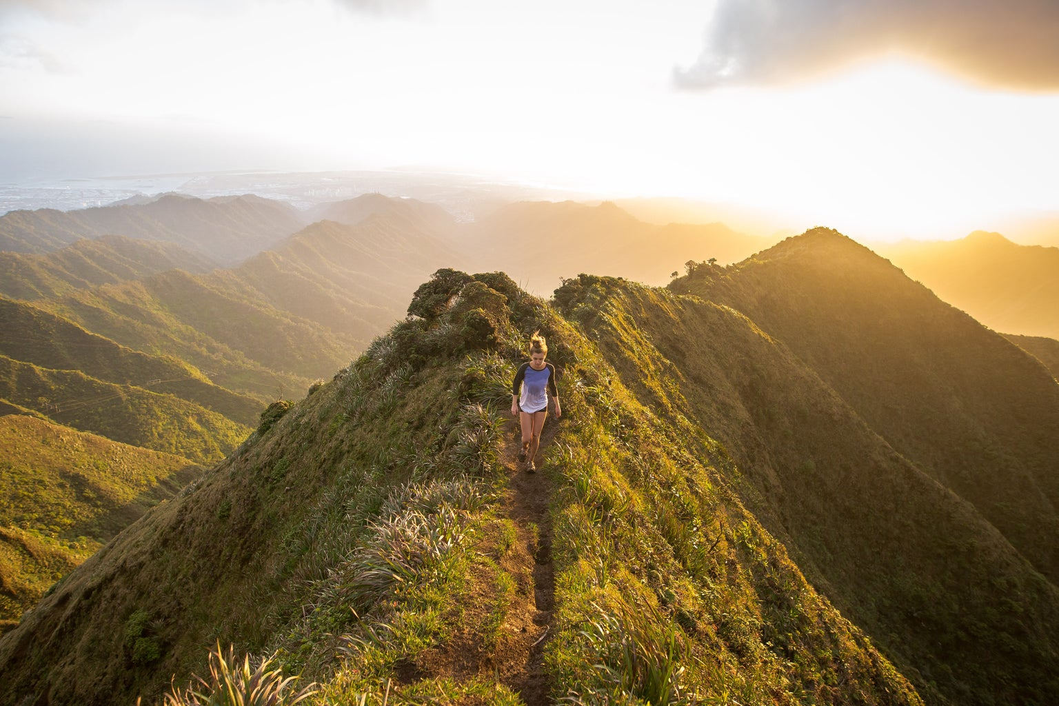 woman walking on a grassy mountain with the sun behind her