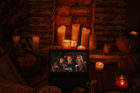 "laptop playing ""Hocus Pocus"" in a room with candles and popcorn"