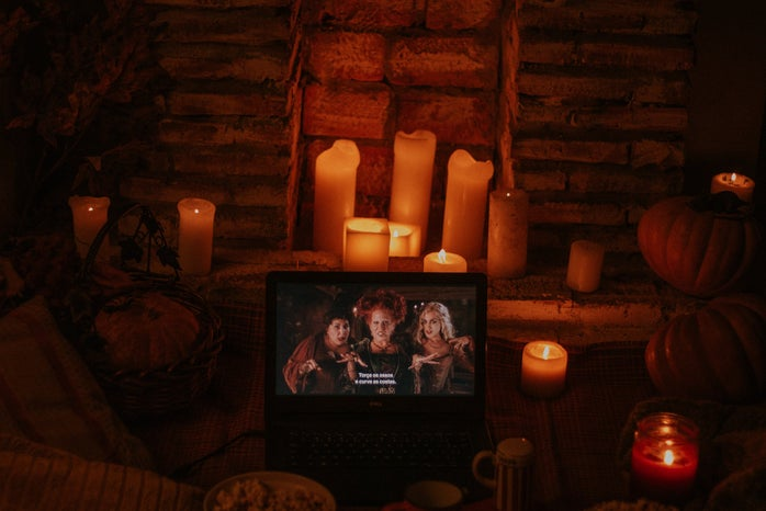 """laptop playing """"Hocus Pocus"""" in a room with candles and popcorn"""