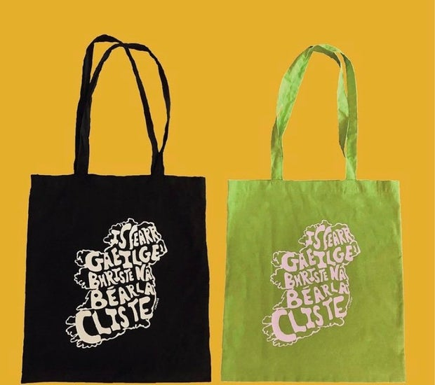 Two tote bags with slogan written in irish on them. Taken and edited by owner of brand