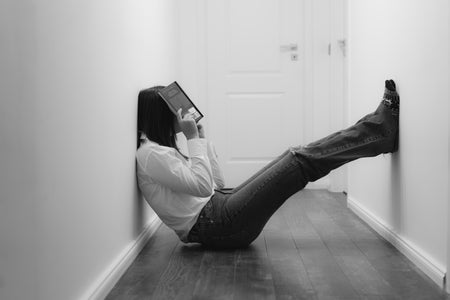 frustrated woman sitting on floor with book