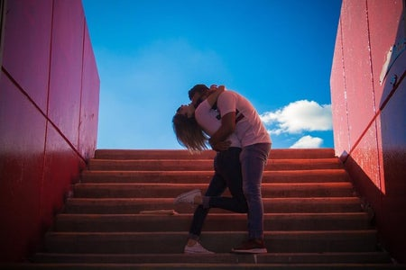 man and woman kissing on stairs