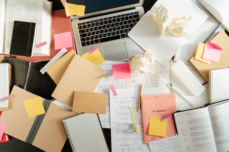 a laptop among a mess of books, notes and crumpled papers
