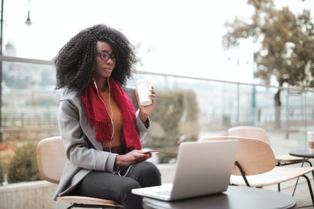 Woman sitting at table with laptop open