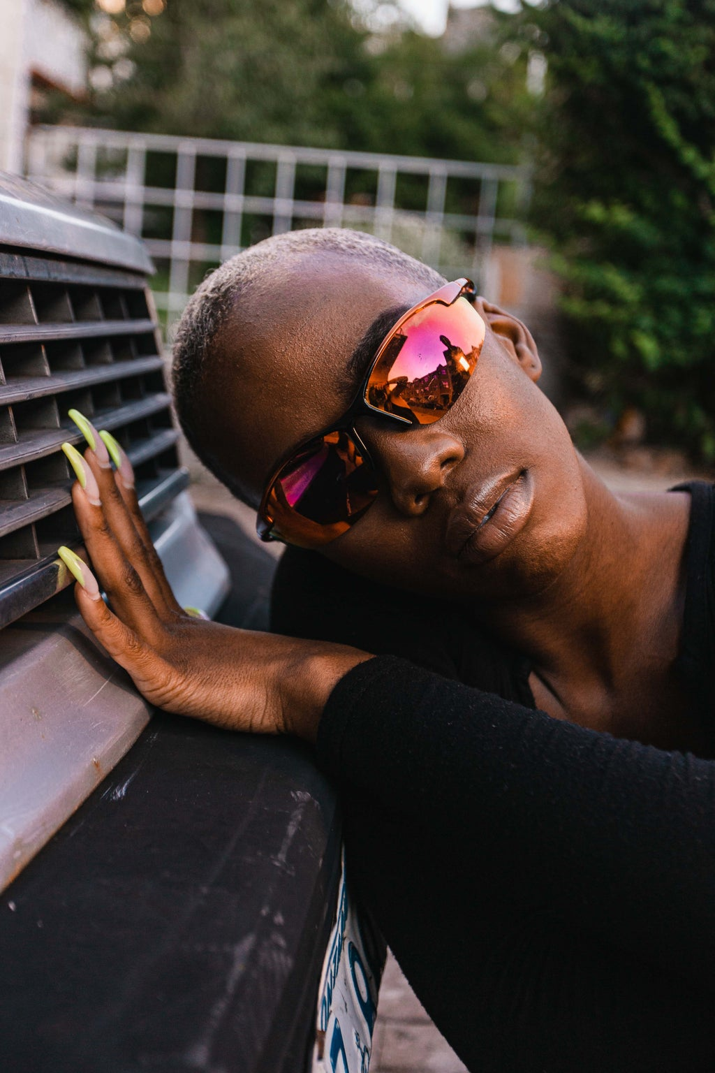 Woman leaning against car wearing sunglasses and acrylic nails