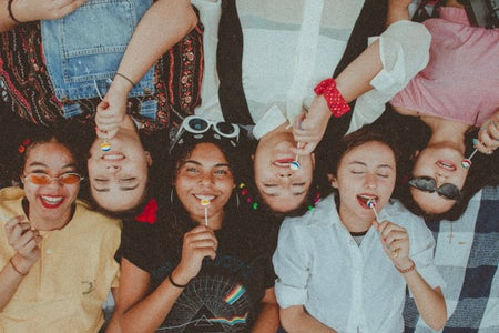 Group of friends side by side with lollipops