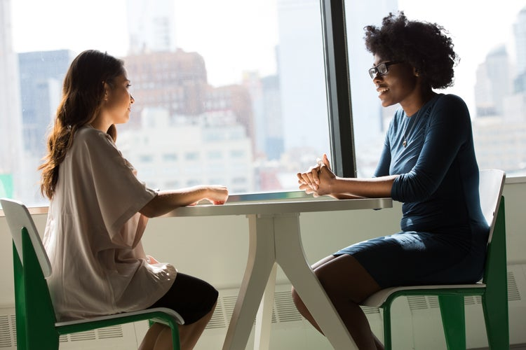 Two women sit at a table and talk