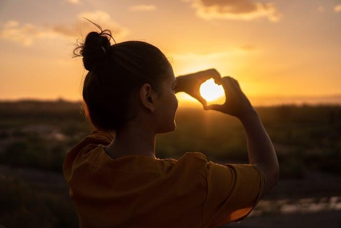 Girl holding heart in sunset