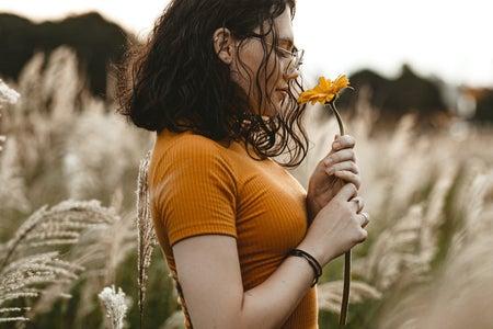 woman in field smelling flower