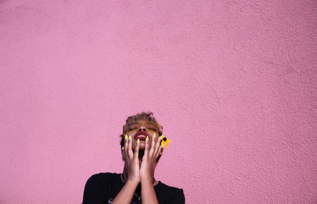 woman standing against a pink wall
