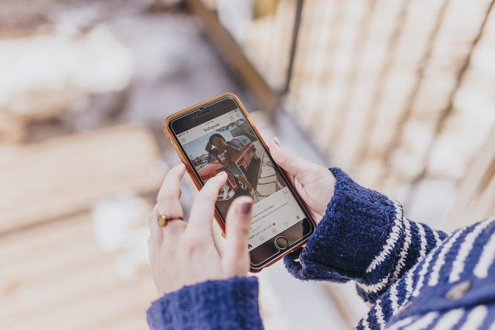 Woman looks at a photo on Instagram on her phone.