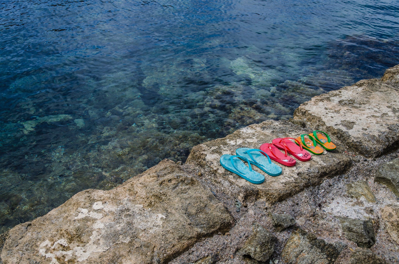 three pairs of flip flops on a cliff