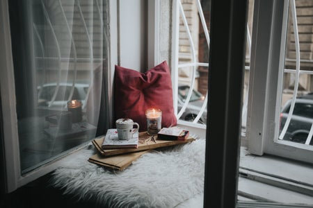coffee, book and candle set by the window with a pillow