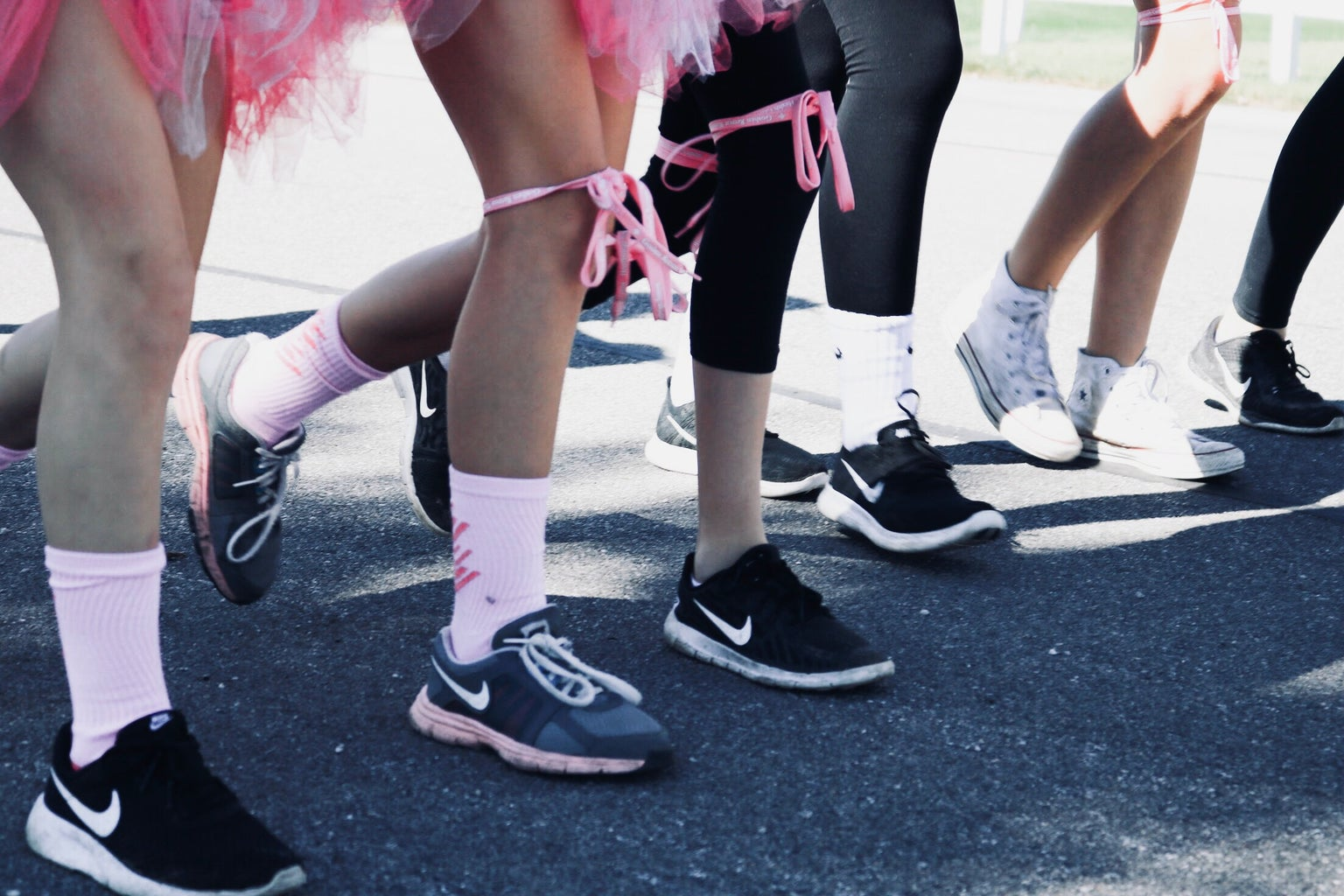 pink ribbon wrapped around group of legs