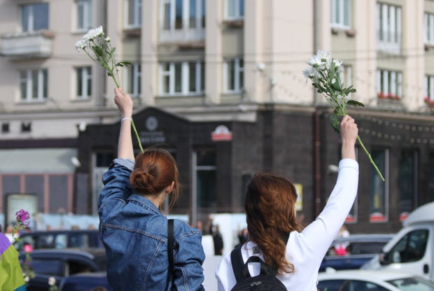 Two girls holding up flowers on a street corner