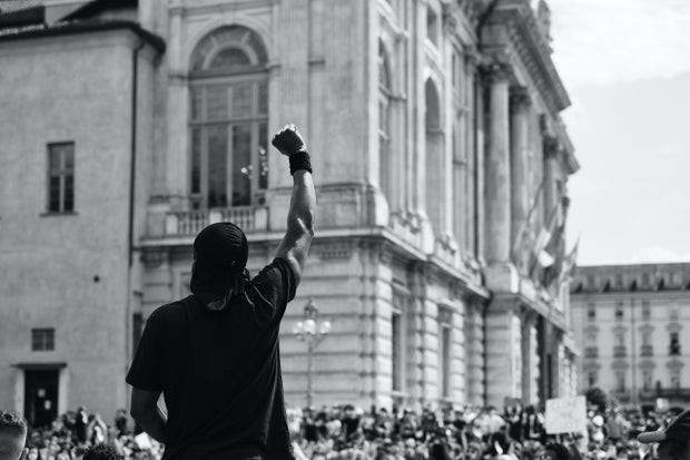 man in black t-shirt standing in front of a crowd with his first raised during a protest