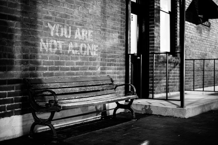 Bench near brick wall with inscription You are not alone