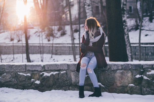 woman in winter clothing is sitting outside in the snow