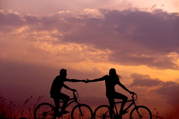 Two people holding hands biking by the sunset